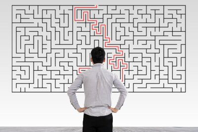 Naklejka Businessman in doubt looking to a maze and searching the way out