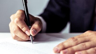 Naklejka Businessman signing a document in office