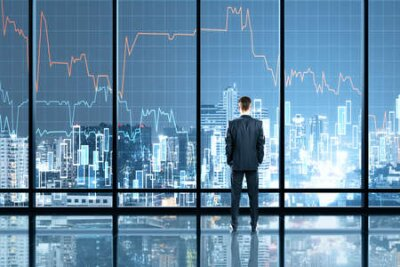 Naklejka Businessman standing in office interior with glowing forex chart hologram. Trade and stats concept. Double exposure