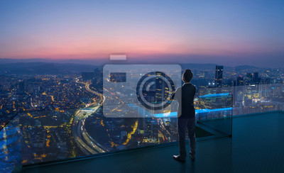 Naklejka Businessman standing on open roof top balcony watching city night view . Business ambition and vision concept .