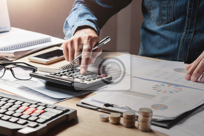 Naklejka businessman working in office with using a calculator to calculate the numbers finance accounting concept