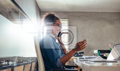 Naklejka Businesswoman in conversation over phone