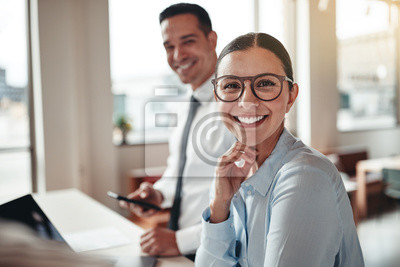 Naklejka Businesswoman smiling while working with a colleague in an offic