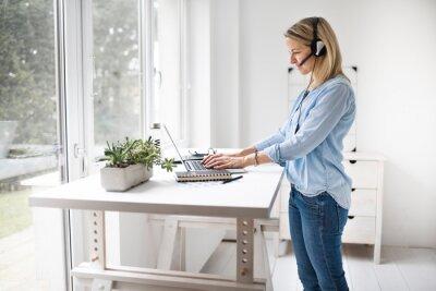 Naklejka Businesswoman working at ergonomic standing workstation