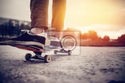 Naklejka But buty deskorolka stoi na przejażdżce deskorolką w zachodzie słońca na drodze, zbliżenie. Koncepcja street sports w nieszczelnych butach