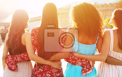 Naklejka Calm women relaxation. Four beautiful girls are posing with their backs to the camera in multicolored dresses, hugging each other like best friends.
