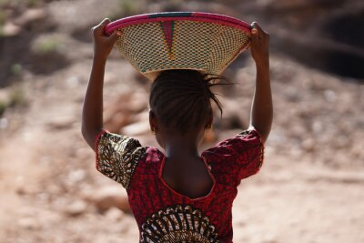 Naklejka Candid Picture of Ethnic African Schoolgirl with Colorful Shirt and Basket