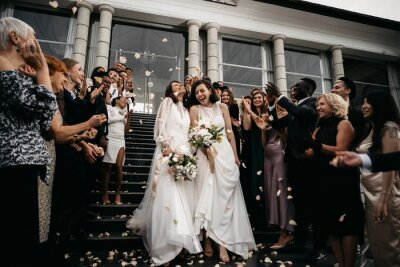 Naklejka Candid shot of two female lesbian LGBT brides walking down the stairs during their wedding ceremony as guests throwing rose petal