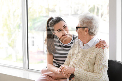 Naklejka Caregiver with senior woman in nursing home