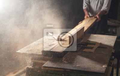 Naklejka Carpenter cutting a wooden plank with a carpentry machine.