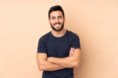 Naklejka Caucasian handsome man isolated on beige background keeping the arms crossed in frontal position