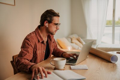Naklejka caucasian male business man working from home typing on laptop drinking hot coffee