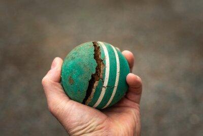 Caucasian man holding broken vintage croquet ball in hand.