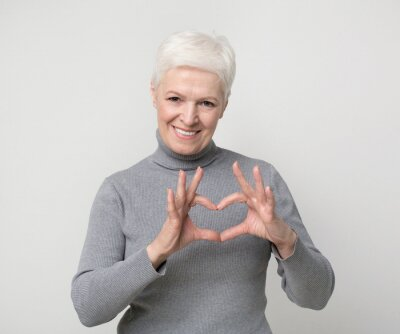 Naklejka Charming aged woman showing heart gesture and smiling