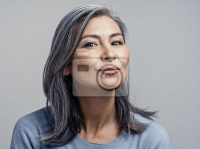 Naklejka Charming Asian mature woman smiles at camera