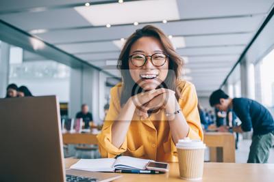 Naklejka Cheerful female freelancer in workspace