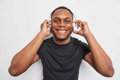 Naklejka Cheerful handsome man with dark skin smiles broadly enjoys listening music via wireless headphones wears black t shirt isolated over white background. People lifestyle entertainment concept.