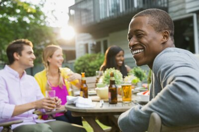 Naklejka Cheerful man with friends having meal at outdoor dining table