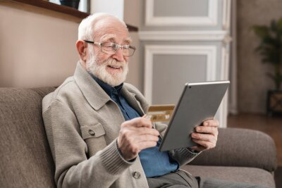 Naklejka Cheerful old grandfather man doing online payment from digital tablet with credit card. Elderly senior caucasian grandpa paying bills online with credit card