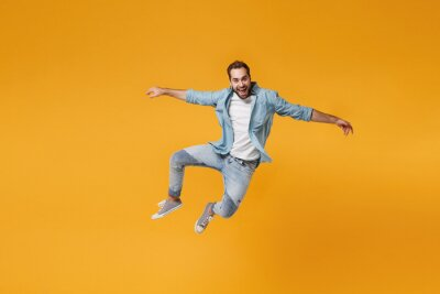 Naklejka Cheerful young bearded man in casual blue shirt posing isolated on yellow orange background, studio portrait. People sincere emotions lifestyle concept. Mock up copy space. Jumping spreading hands.