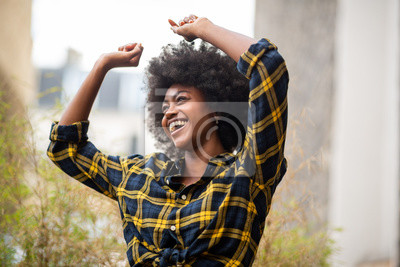 Naklejka cheerful young carefree afro woman with arms raised and smiling outside