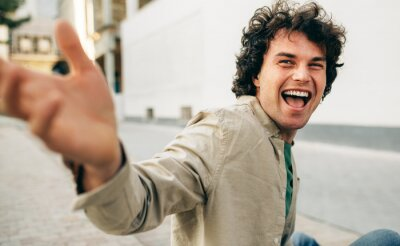 Naklejka Cheerful young man with curly hair, smiling and looking to the camera, feeling joyful, sitting on the city street outdoors. Happy smart student male meeting with his friends. People, emotion