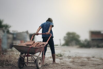 Naklejka Child labor in building commercial building structures. World Labor Day concept