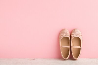 Naklejka Child shiny low shoes with glitters and straps on wooden floor at light pink wall. Pastel color. Closeup. Front view. Empty place for text.