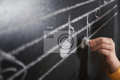 Naklejka Child writing music notes on blackboard, closeup
