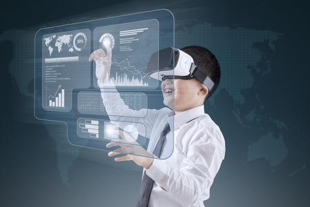 Naklejka Chłopiec jest ubranym rzeczywistości wirtualnej słuchawki podczas gdy dotykający pieniężnego wykres na wirtualnym ekranie