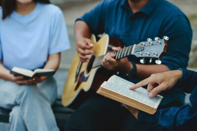 Naklejka Christian families worship God in the garden by playing guitar and holding a holy bible. Group Christianity people reading the bible together.Concept of wisdom, religion, reading, imagination.