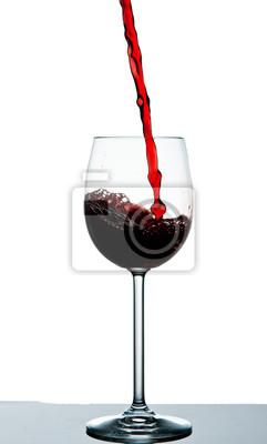 Ciemno czerwone wino wlewa się do kieliszka