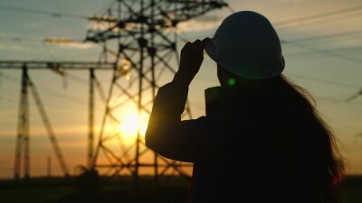 Naklejka Civil engineer, woman specializing in electricity supply works outdoors. Environmentally friendly electricity. Modern technologies. Power engineer in safety helmet checks power line, digital tablet