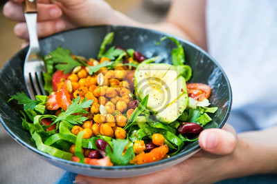 Naklejka Clean eating, vegan healthy salad bowl closeup , woman holding salad bowl, plant based healthy diet with greens, chickpeas and vegetables