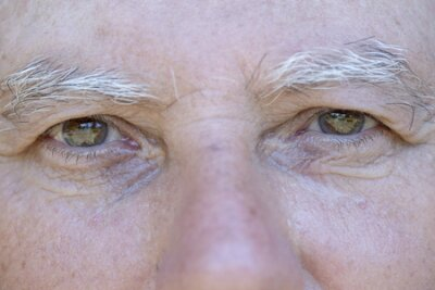 Naklejka Close up eye of caucasian old man. Portrait of old man outdoors. Caucasian male face background, close up eyes, macro