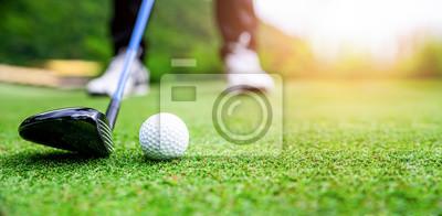 Naklejka Close up golf ball on green grass field