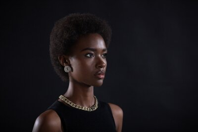 Naklejka Close up half turn portrait of african american woman with afro hairstyle on black studio background.