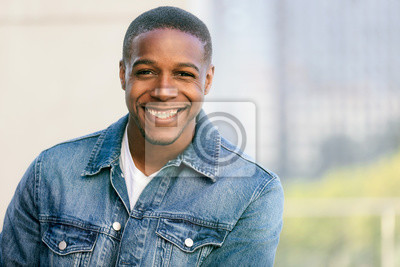 Naklejka Close up head shot of a handsome commercial african american model with perfect white teeth smile after dentist, dental and orthodontic advertisement