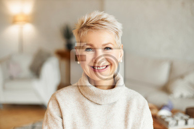 Naklejka Close up image of happy good looking elegant fifty year old woman wearing warm cozy jumper, pearl earrings and short stylish hairdo being in good mood sitting in living room, smiling broadly at camera