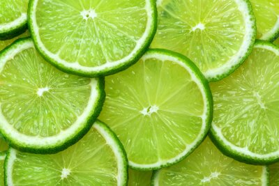 Naklejka Close-up juicy Lime slices abstract background in pastel green color. Bright summer texture.