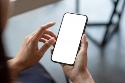 Naklejka Close-up of a businessman hand holding a smartphone white screen is blank the background is blurred.Mockup.