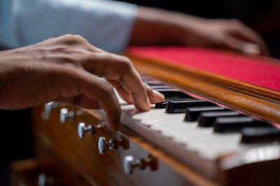 Naklejka Close up of Hands playing Harmonium or reed organ an Indian classical music instrument.