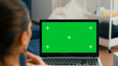 Naklejka Close up of laptop computer with mock up green screen chroma key display. Business woman lying on sofa and typing on isolated pc for commerce project in home office