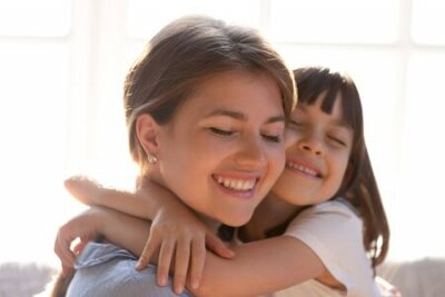Naklejka Close up of loving young mom and little daughter hug cuddle showing care and affection, cute small girl child embrace happy mother or nanny, enjoy tender sweet moment at home together
