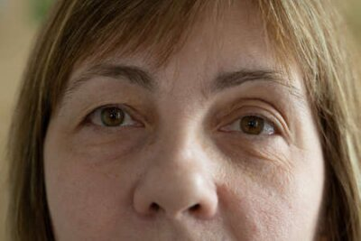Naklejka Close up of senior woman face and eye. Eyes of an elderly woman with wrinkles on the eyelids