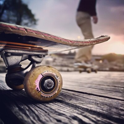 Naklejka Close-up Of Skateboard With Blurred Man Skateboarding Behind