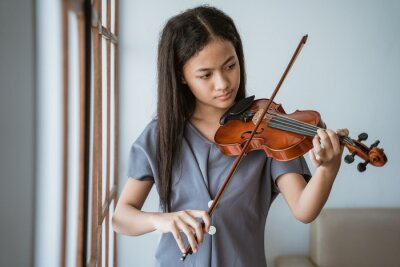 Naklejka close up of teenage girl learn to play a violin instrument beside the window in a room at home