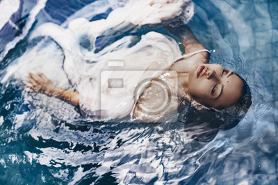 Naklejka close up portrait of beautiful woman lying in water with fabric. Fashion concept