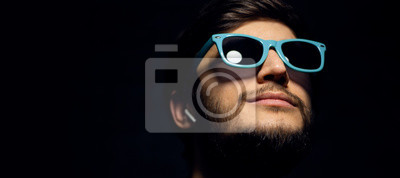 Naklejka Close-up portrait of young guy with wireless earphones, looking up, wearing blue sunglasses, isolated on black background.
