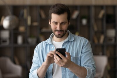 Naklejka Close up satisfied man using phone, looking at screen, standing at home, positive young male holding smartphone, chatting in social network with friends or shopping online, enjoying leisure time